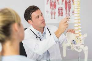 An alternate angle of a doctor holding a spinal replica